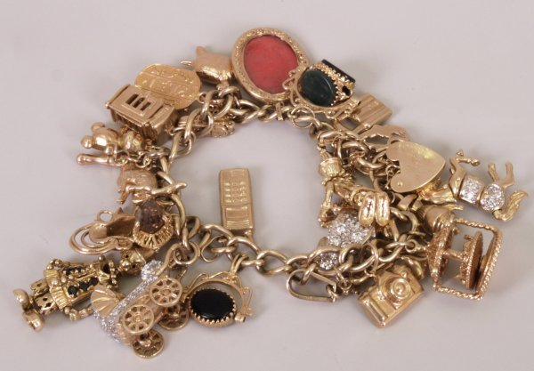 11: 9ct gold stretched curb link charm bracelet with tw