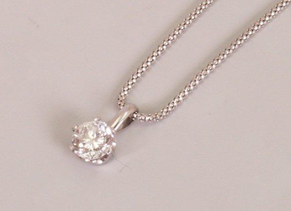 12:  A single stone round brilliant diamond set pendant