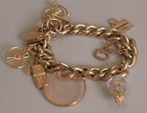 20: 9ct gold curb link charm bracelet, set with seven c