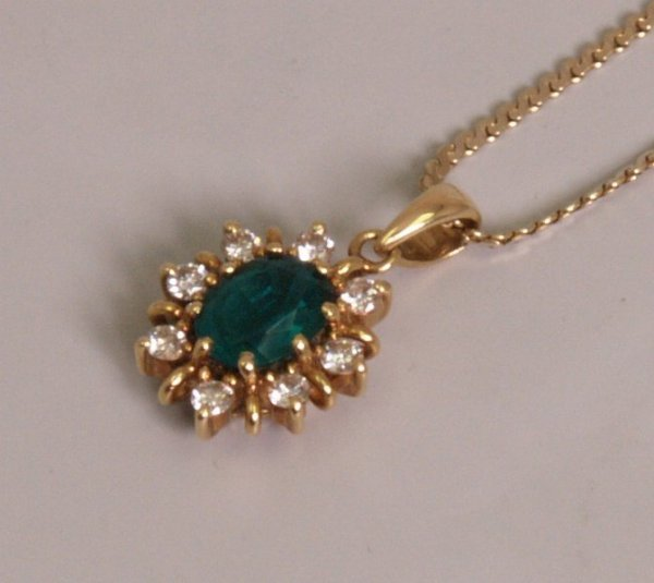 102: 18ct gold emerald and diamond set cluster pendant,