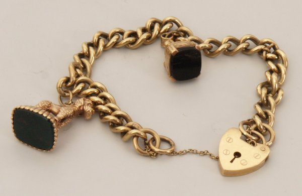 110: 9ct gold solid curb link bracelet with two charms