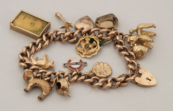 114: 9ct gold curb link chain charm bracelet with thirt