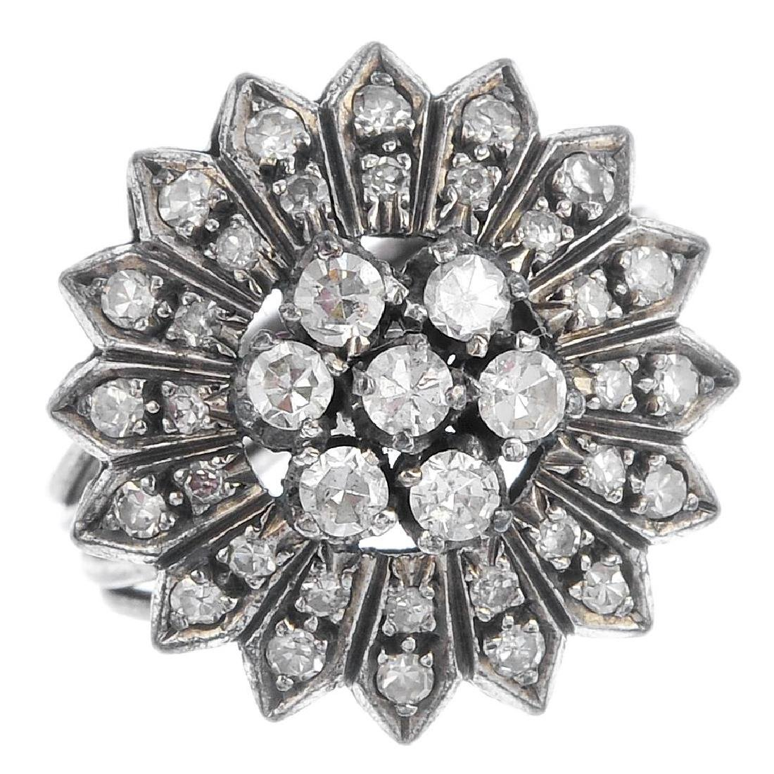 A diamond cluster ring. Of floral design, the