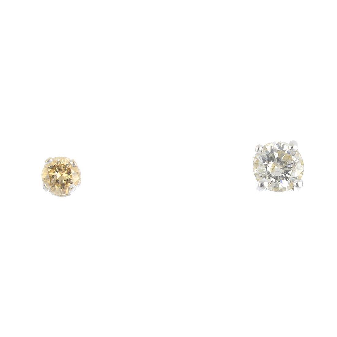 Two single brilliant-cut diamond stud earrings.
