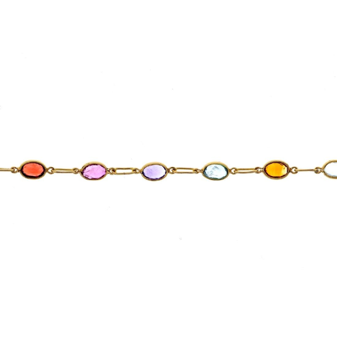 A gem-set bracelet. Designed as a series of oval-shape