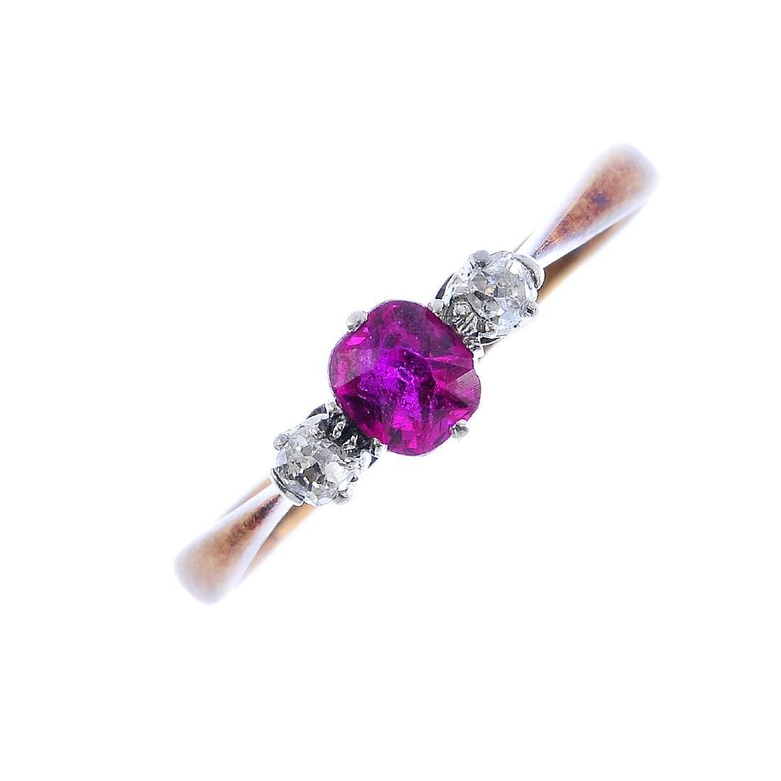 A ruby and diamond three-stone ring. The cushion-shape