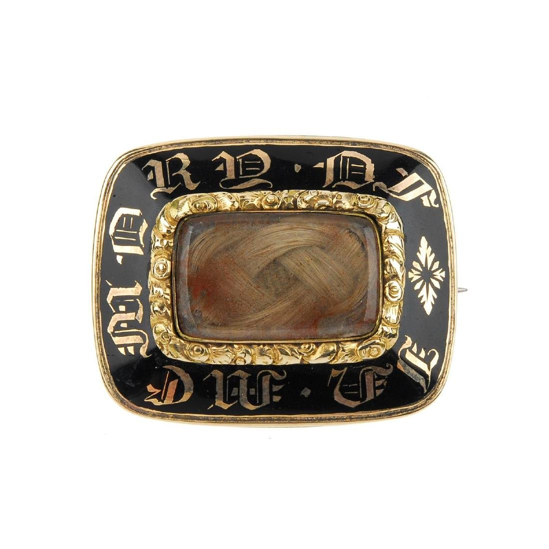 An early Victorian gold black enamel mourning brooch.