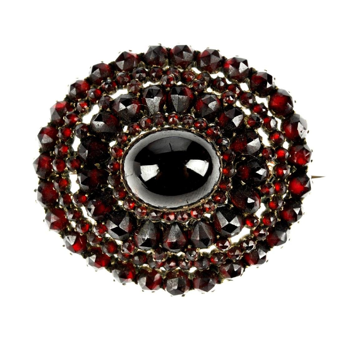 A late 19th century garnet brooch. Of oval outline, the