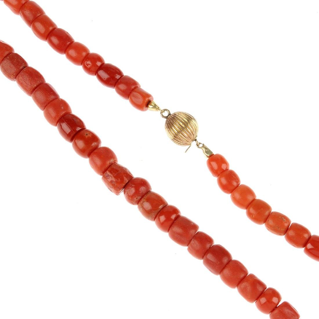 A coral necklace. The single row of barrel-shape beads,