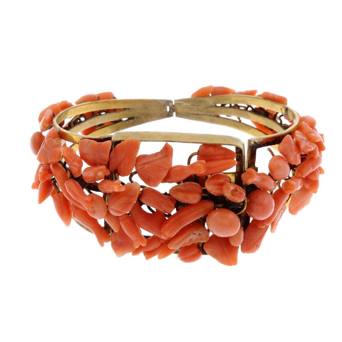 A coral bangle. The hinged bangle set with floral and