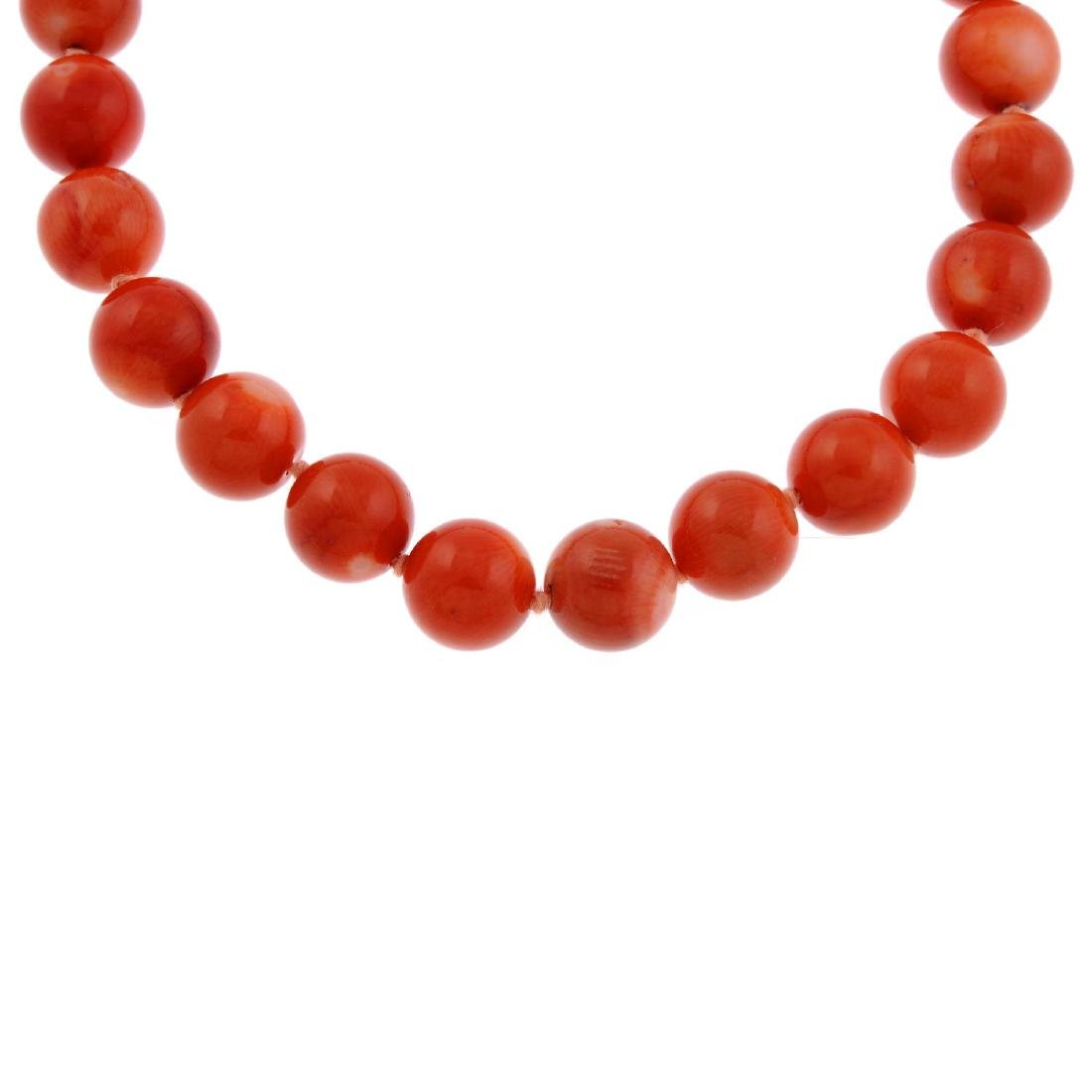 A dyed coral bead necklace. A single row of twenty-nine