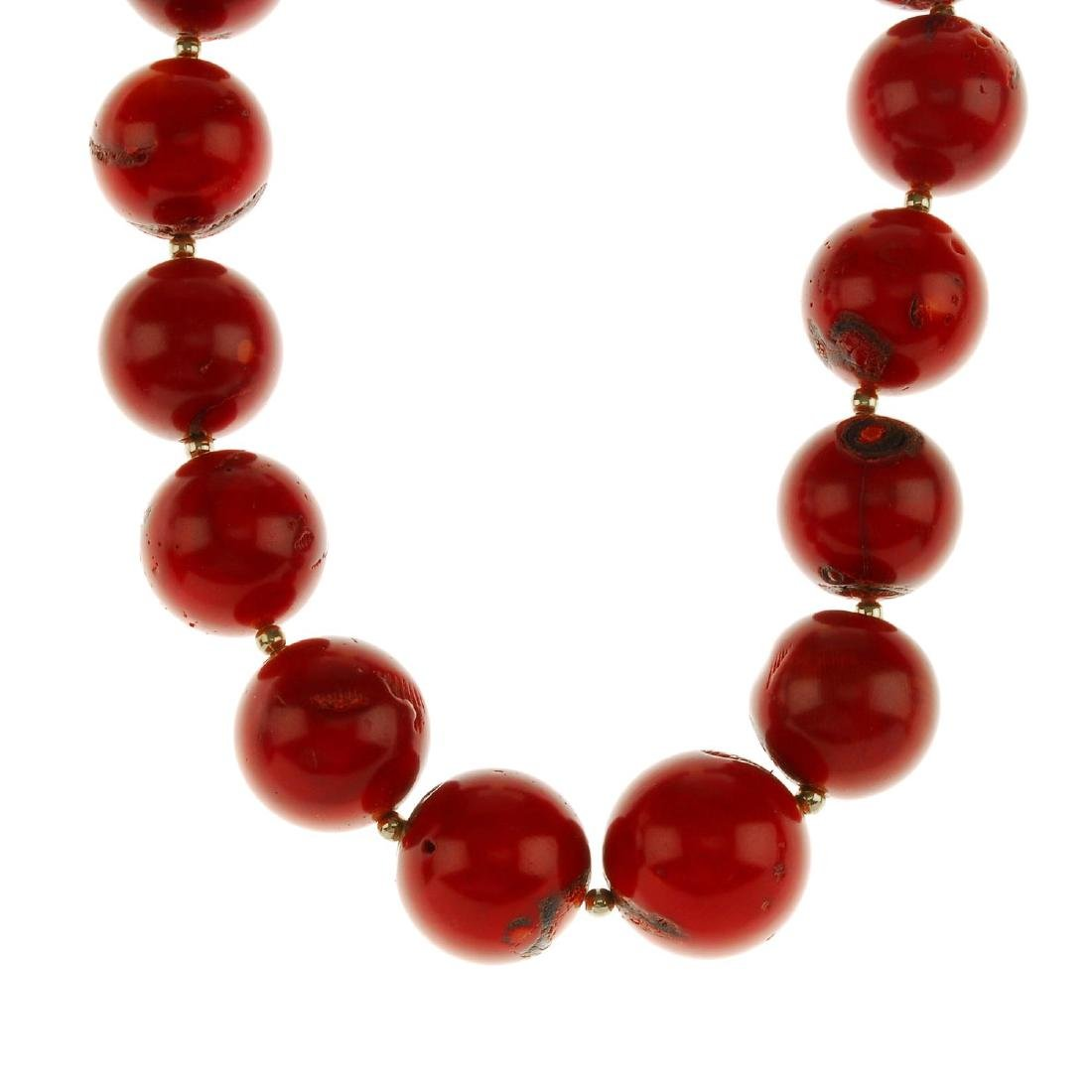 A dyed coral bead necklace. Comprising sixteen