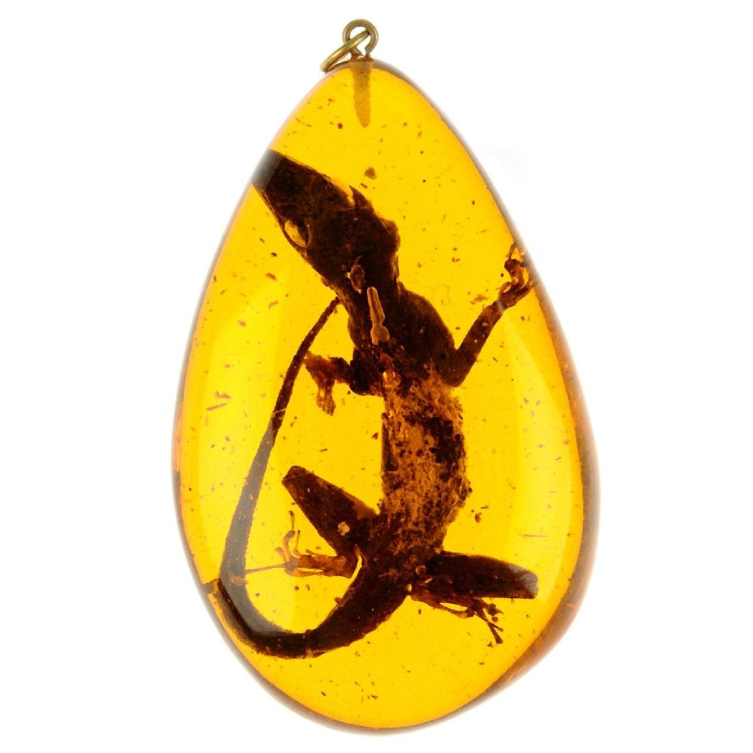 A man-made resin pendant with enclosed gecko. Of