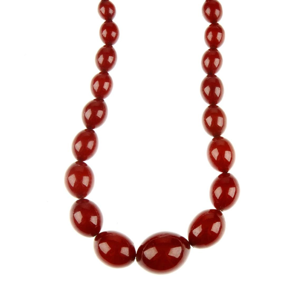 A red plastic bead necklace. Designed as graduated
