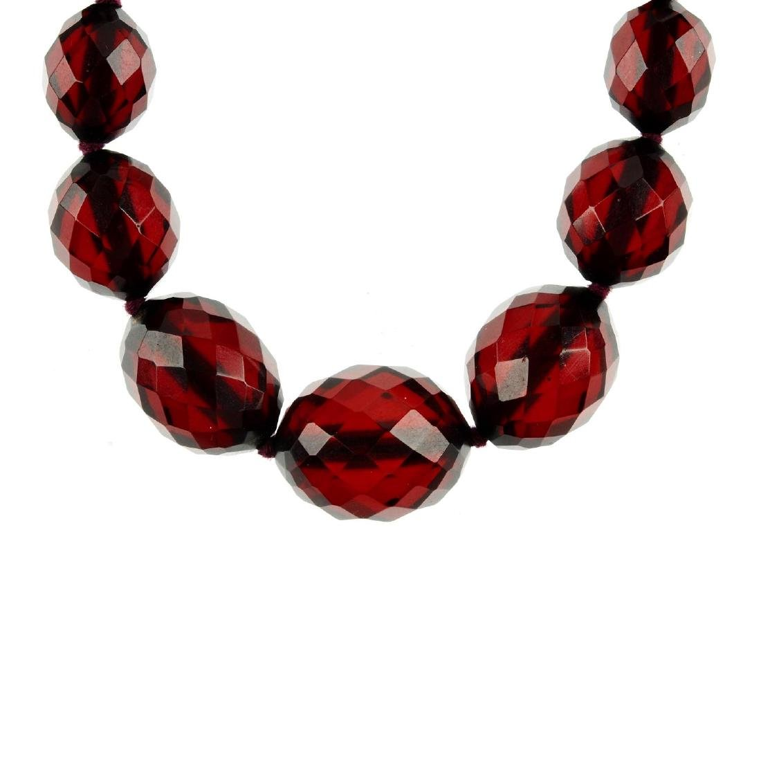 A bakelite necklace. Comprising a single row of faceted