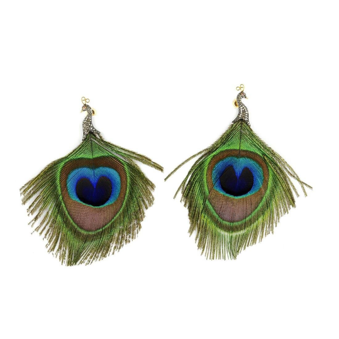 A pair of peacock feather and diamond earrings. The