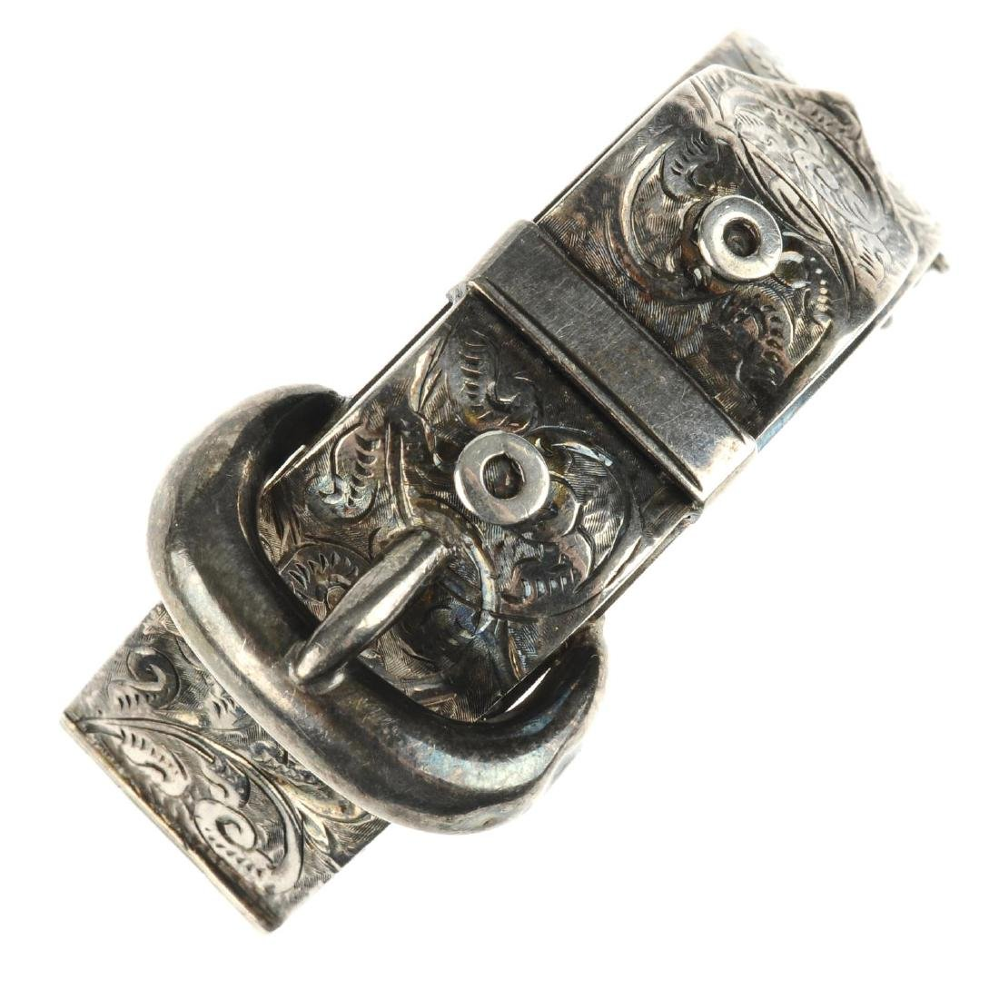 A late Victorian silver hinged buckle bangle. With