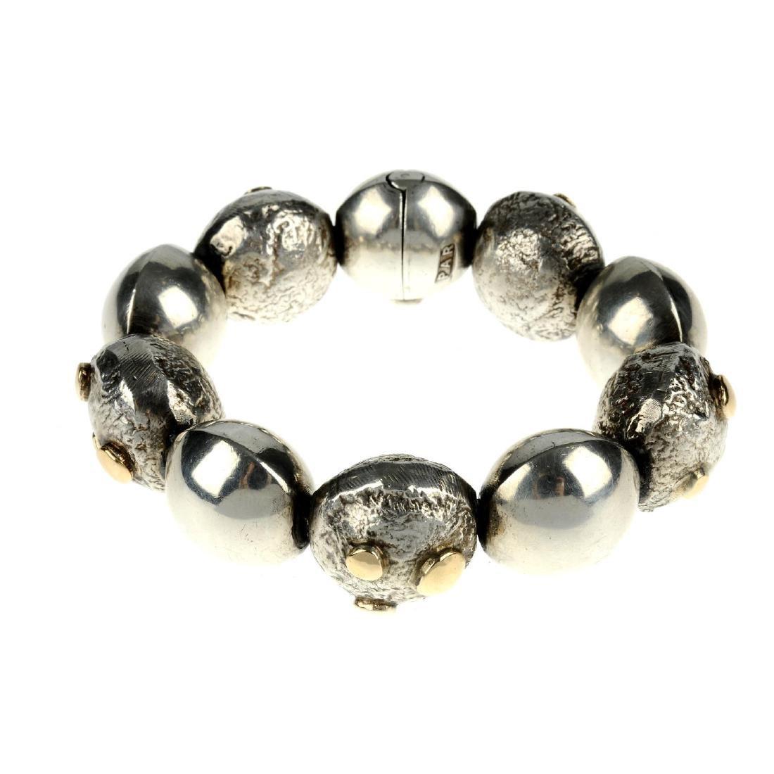 A silver bracelet. Designed as ten circular beads,