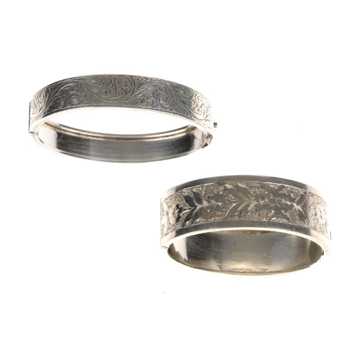 Two hinged bangles. The first a silver bangle with