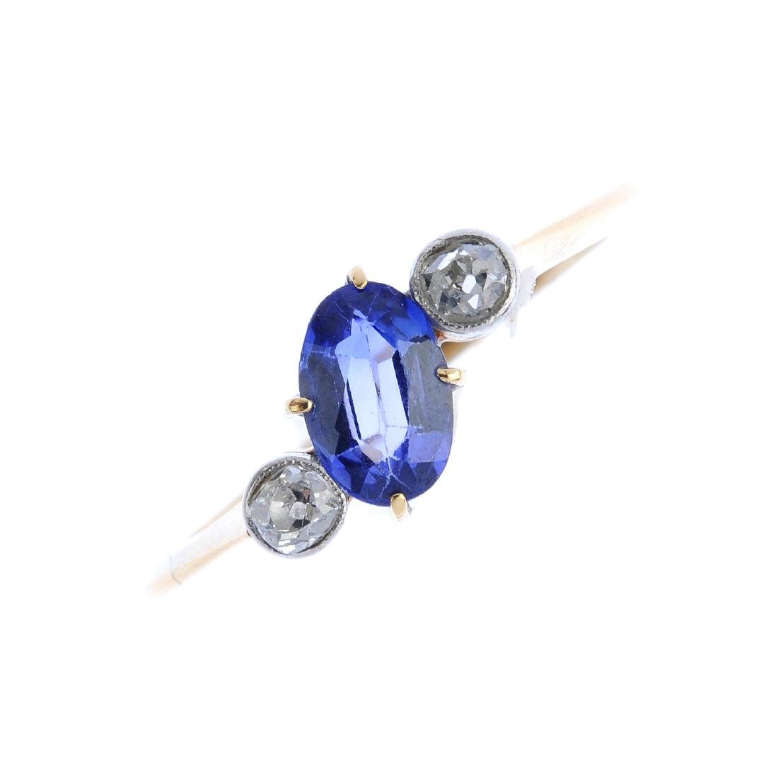 A sapphire and diamond three-stone ring. The off-set