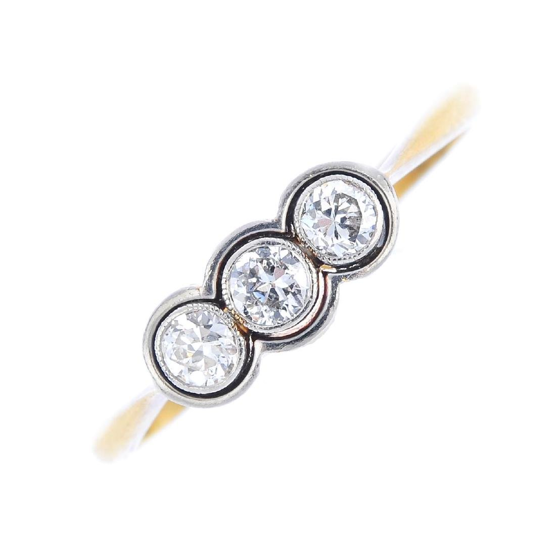 A diamond three-stone ring. The brilliant-cut diamond