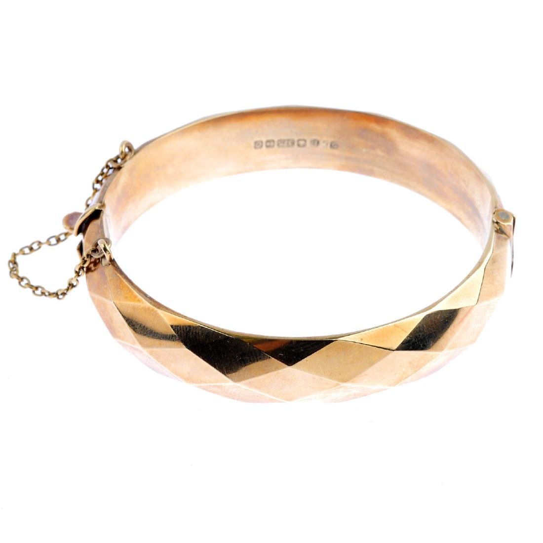 A 9ct gold hinged bangle. The geometric front, with