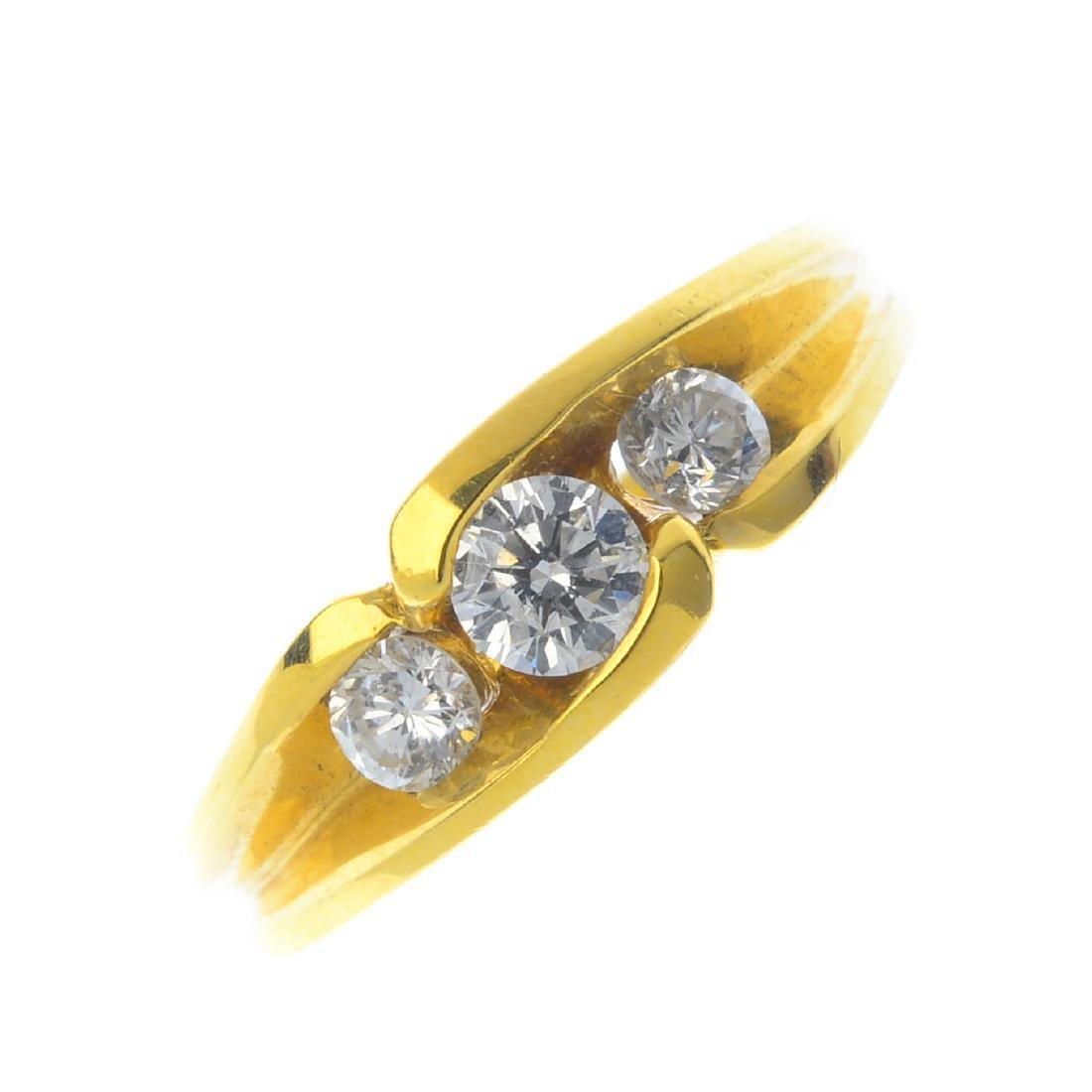 An 18ct gold diamond three-stone ring. The graduated