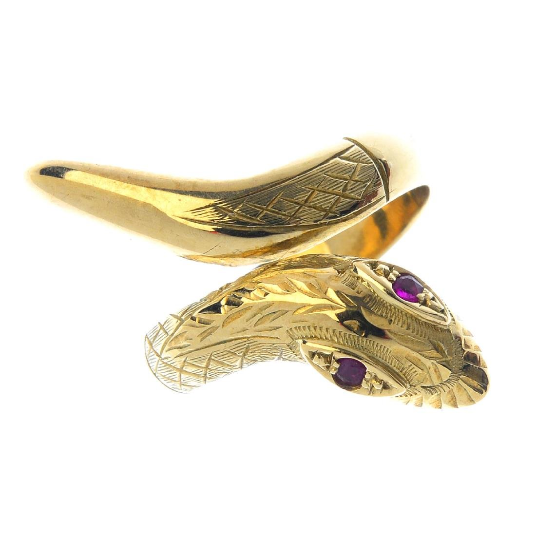 A 9ct gold ruby snake ring. Designed as a textured