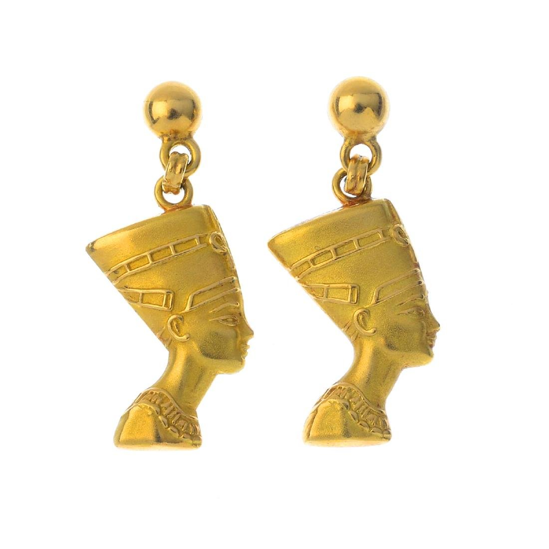 A pair of earrings. Each designed to depict a textured