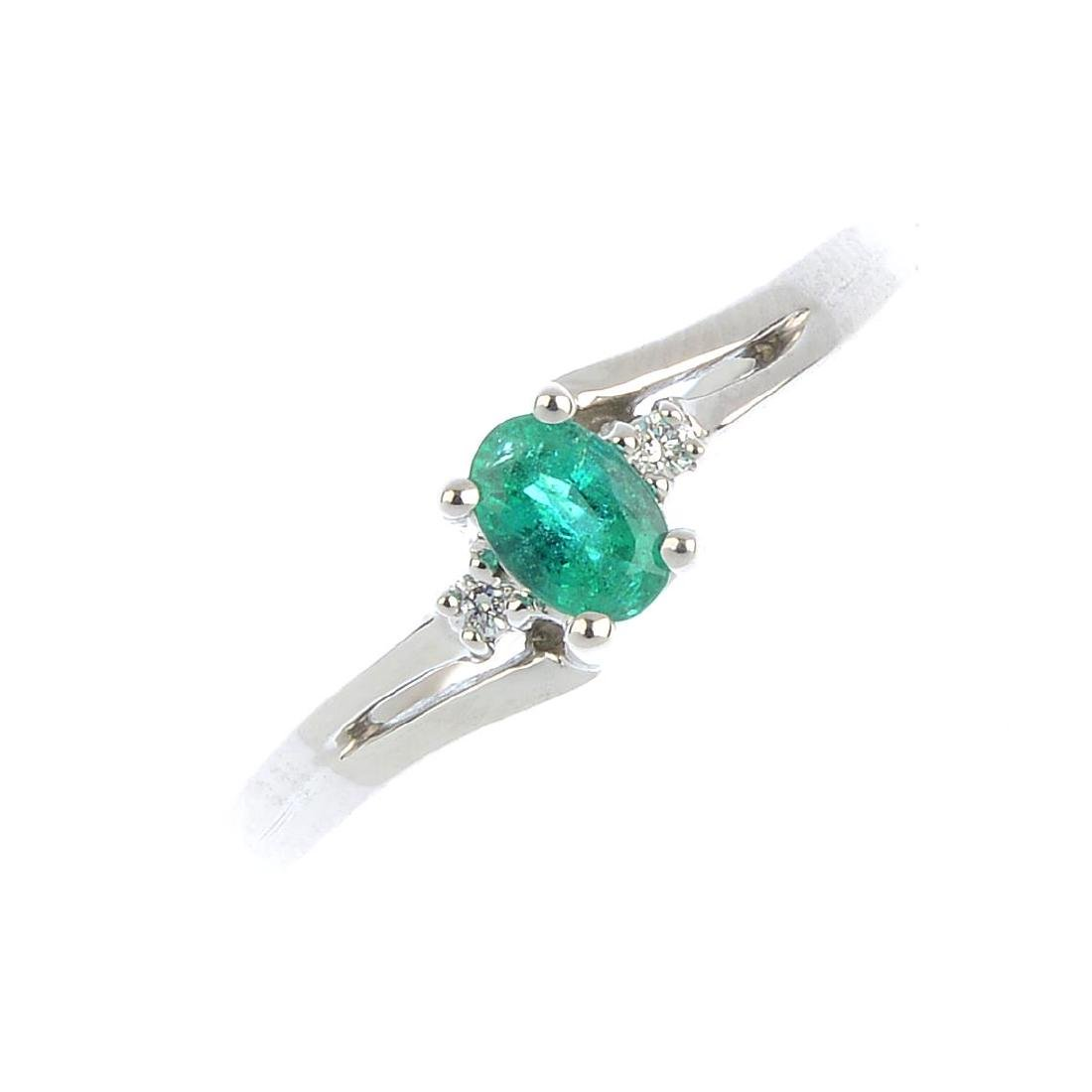 An emerald and diamond ring. The oval-shape emerald,