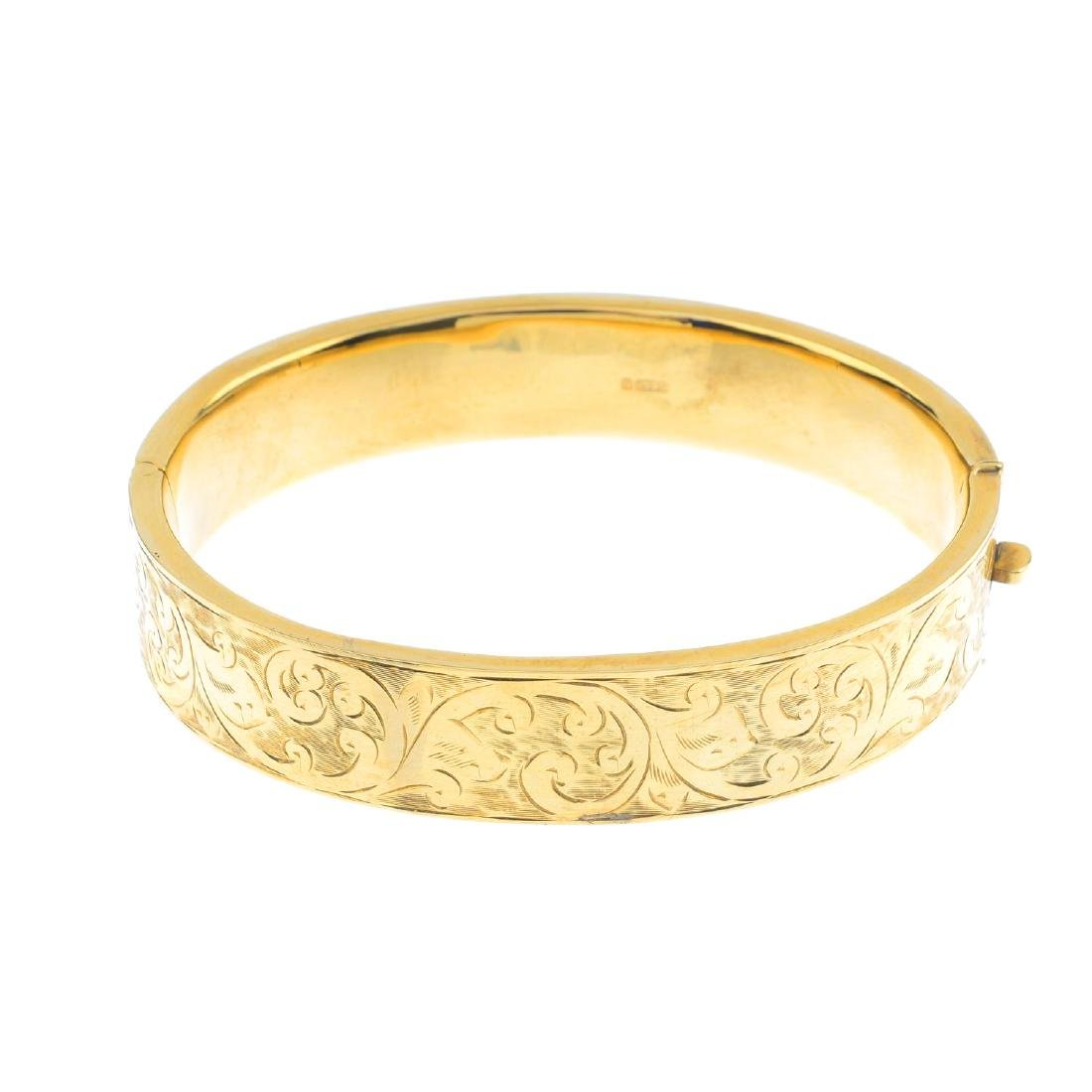 A 1960s 9ct gold hinged bangle. Designed as a scrolling