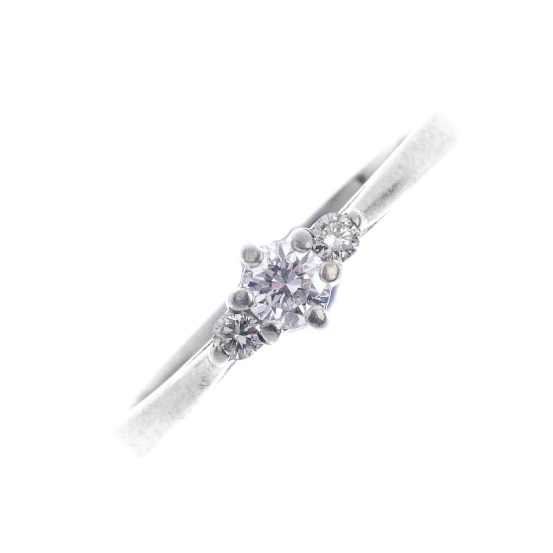 A platinum diamond three-stone ring. The graduated