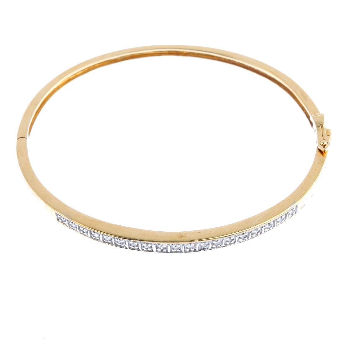 A 9ct gold diamond hinged bangle. The single-cut