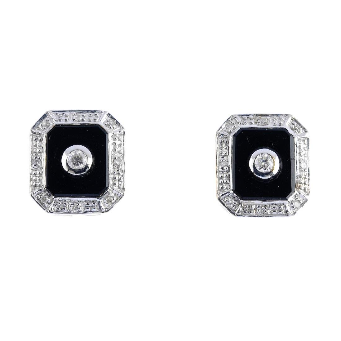 A pair of onyx and diamond stud earrings. Each designed