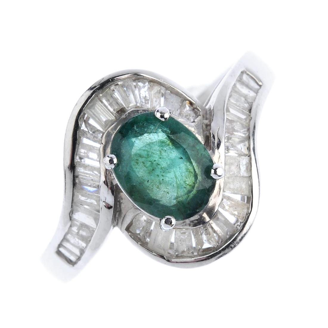 An emerald and diamond crossover ring. The oval-shape