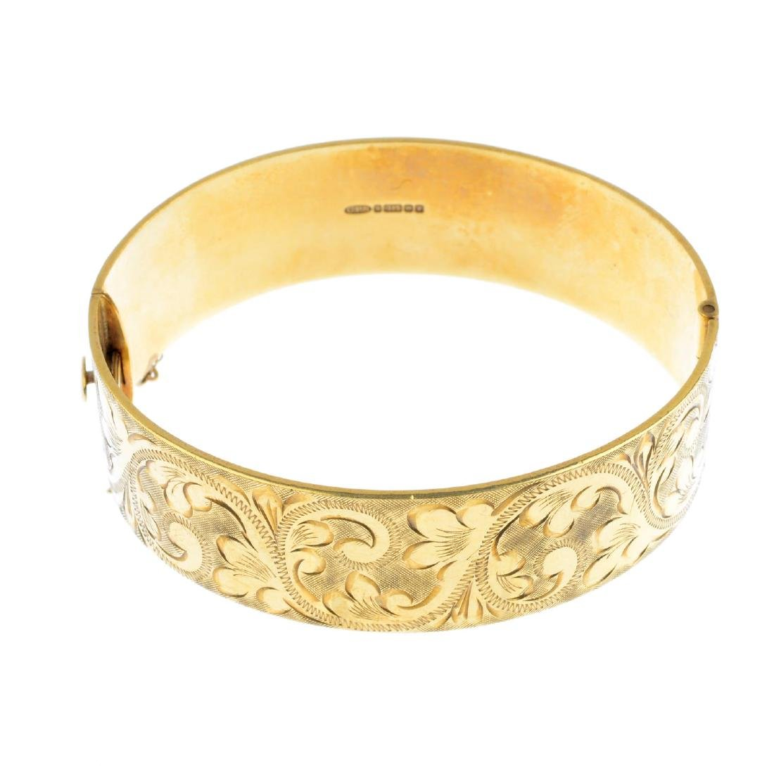 A 1970s 9ct gold hinged bangle. With engraved foliate