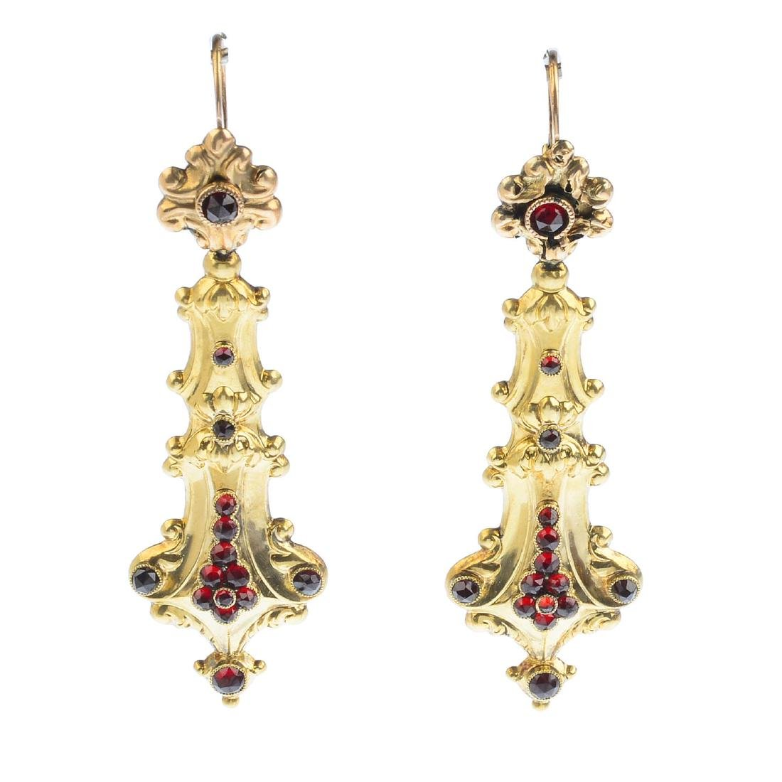 A pair of garnet earrings. Each designed as a tapered