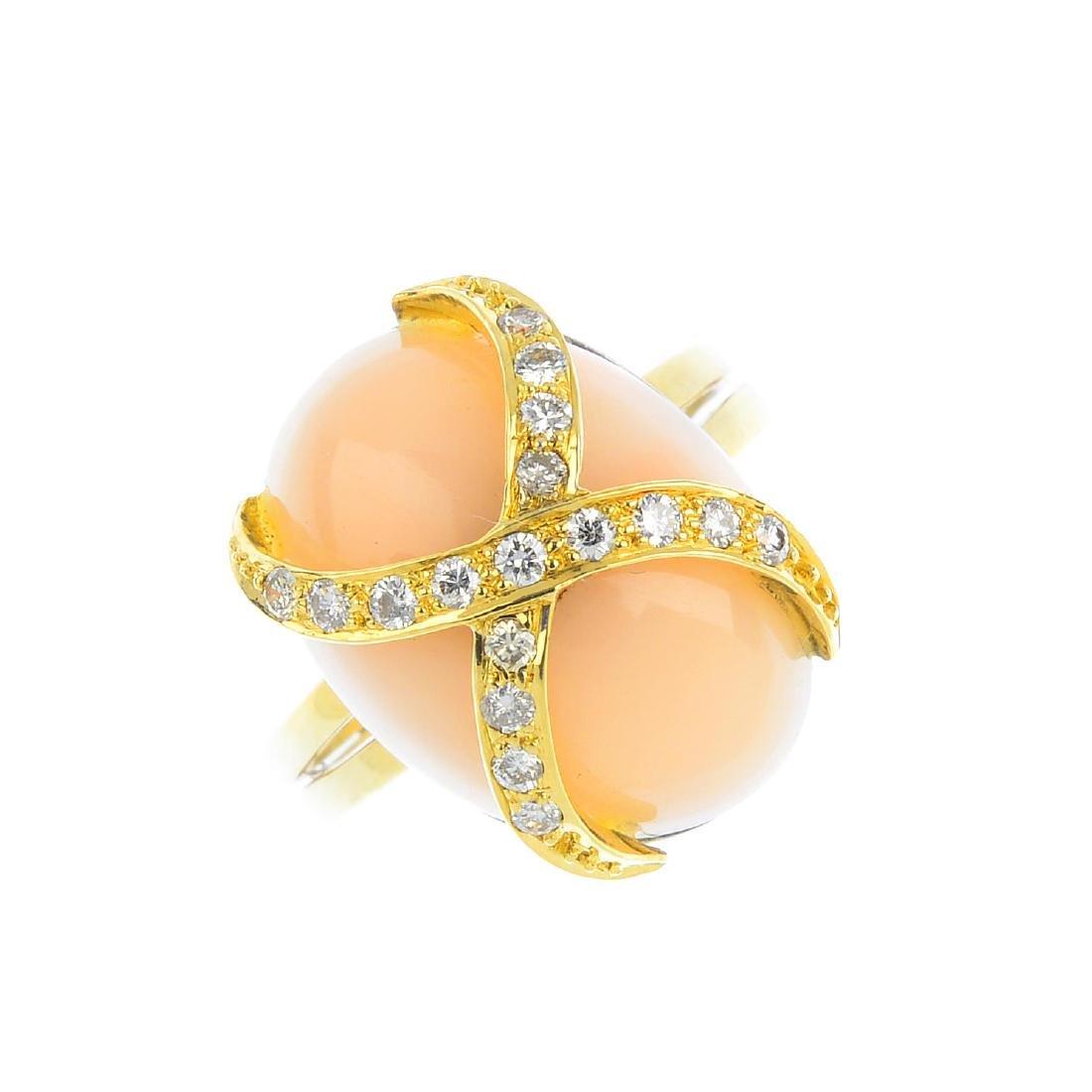 A coral and diamond ring. The brilliant-cut diamond