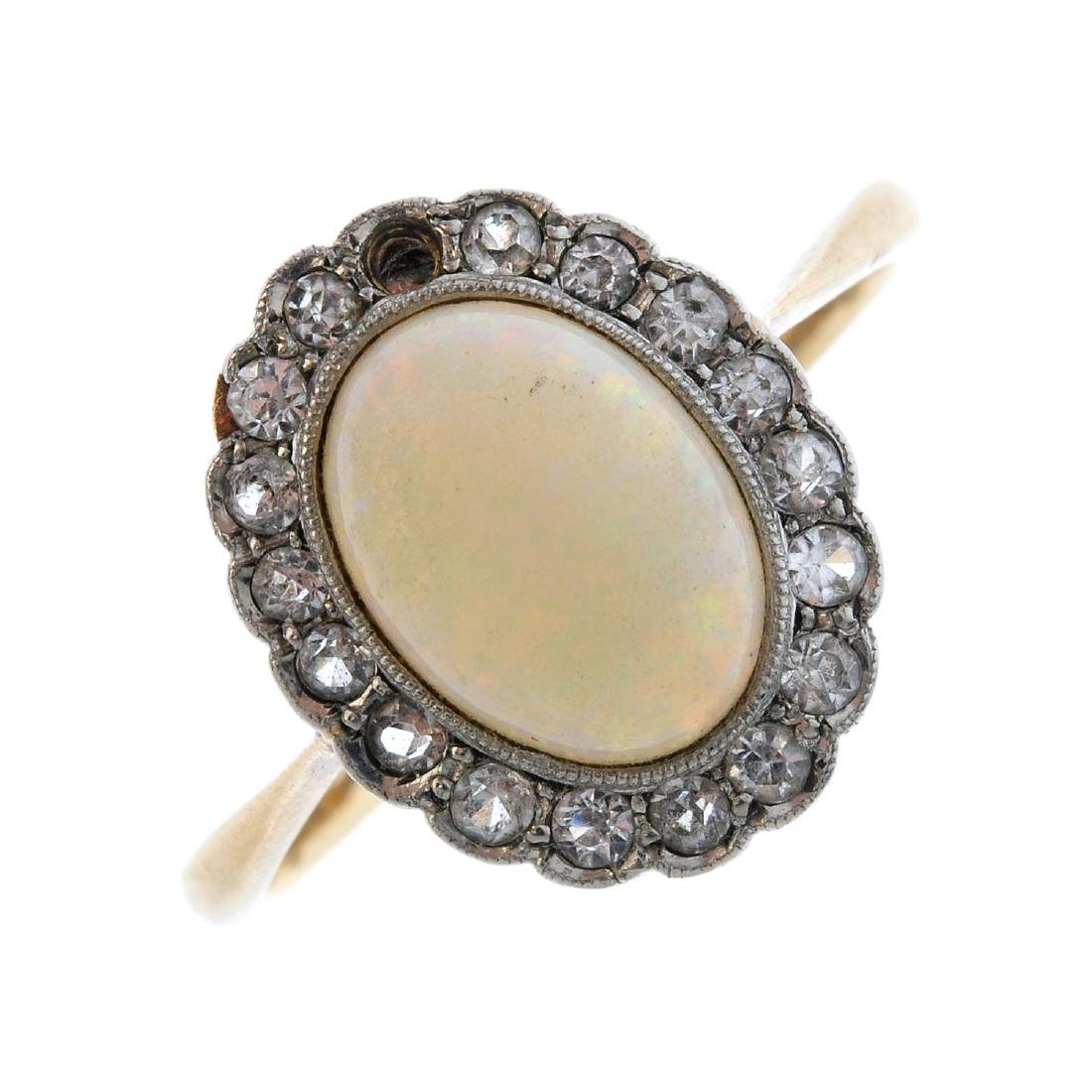 An opal and cubic zirconia cluster ring. The oval opal