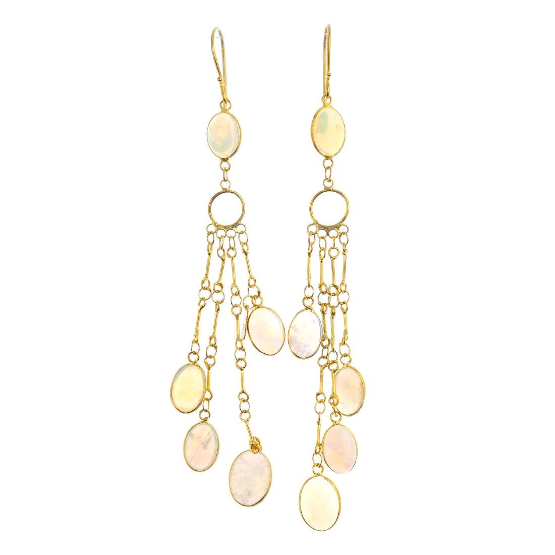 A pair of opal earrings. Each designed as four oval