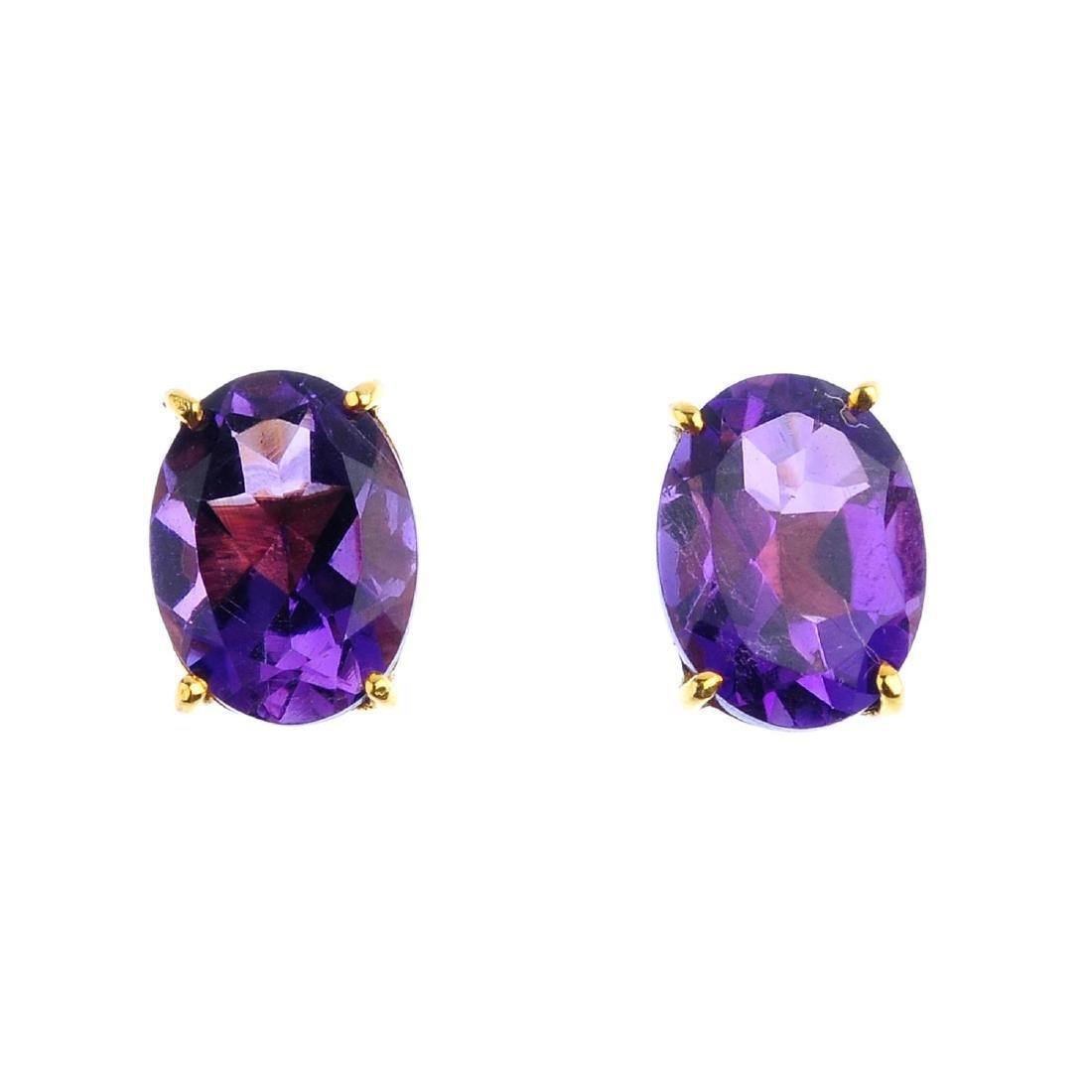 A pair of oval-shape amethyst stud earrings. Length