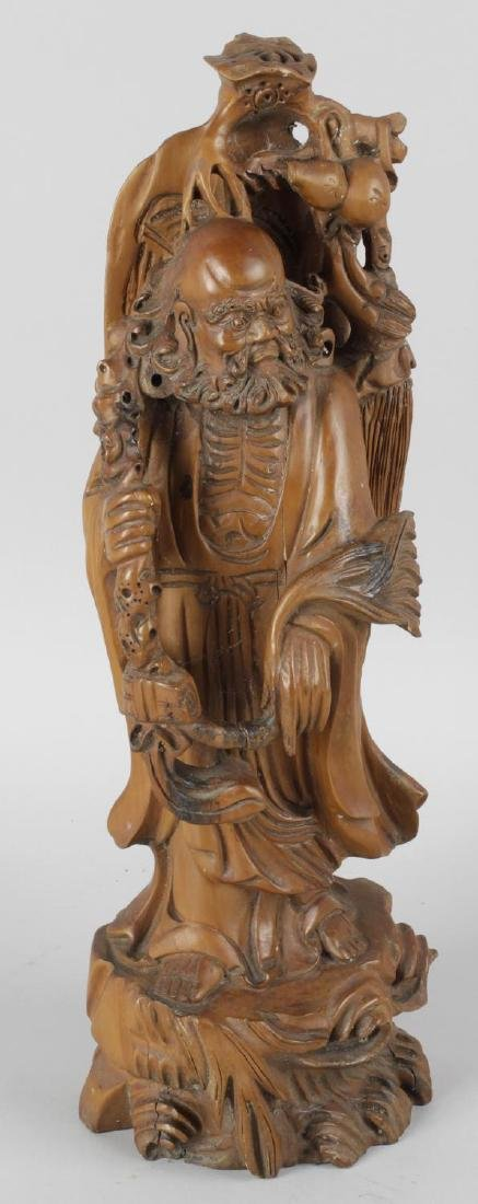 A Chinese hardwood carving, modelled as an immortal