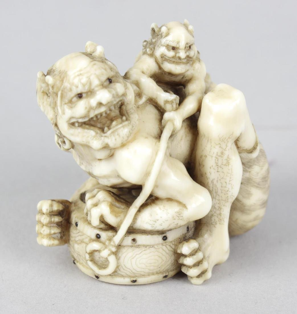 A good Japanese Meiji period ivory netsuke of two oni,