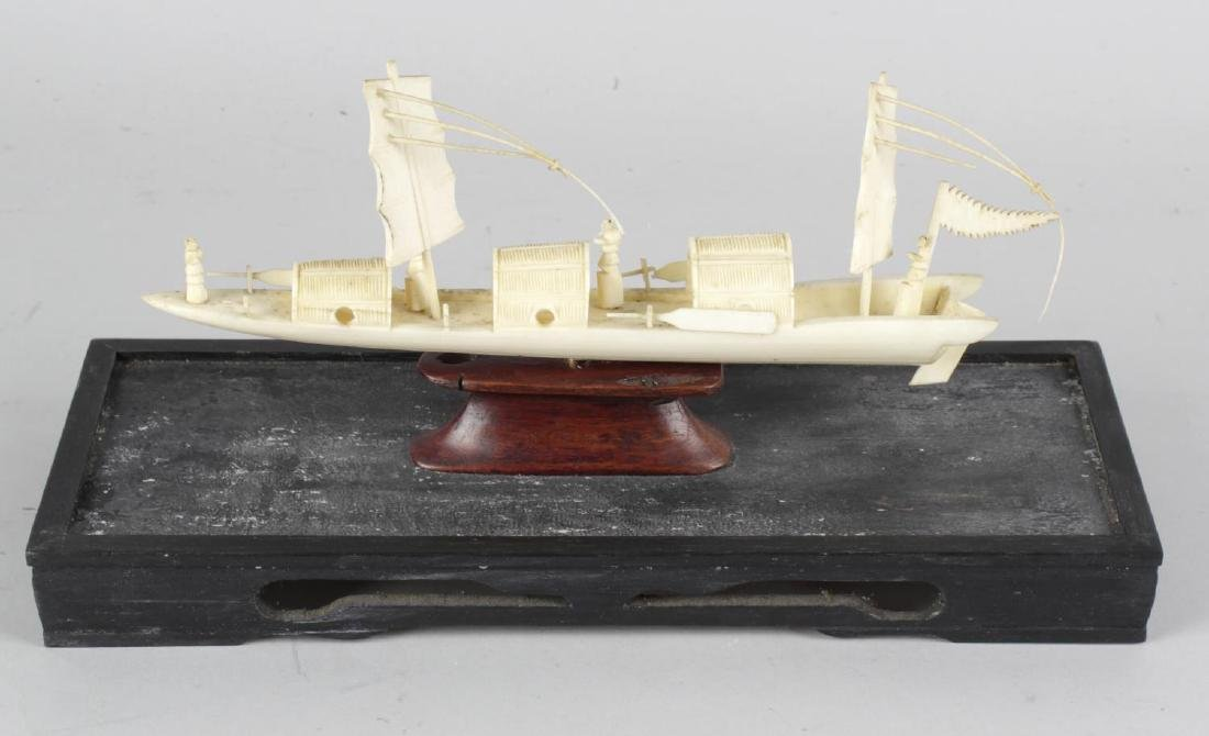 A Chinese carved ivory model of a sailing boat or junk.