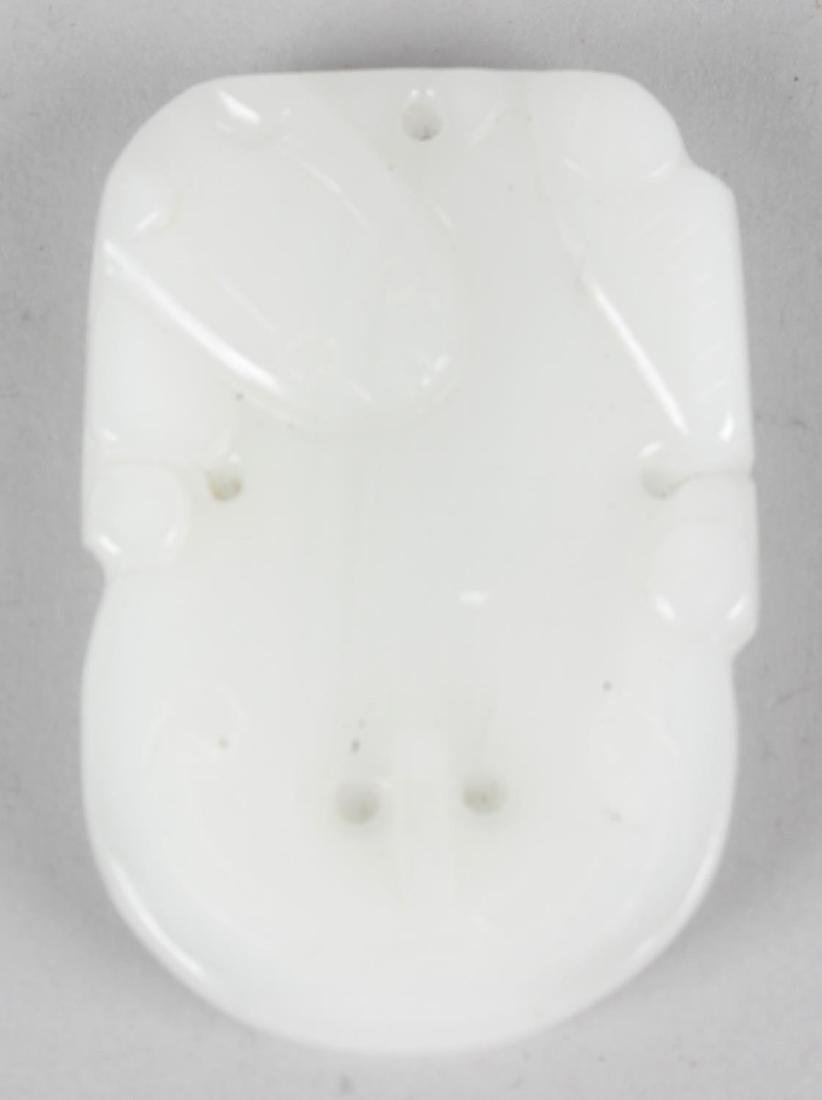 A Chinese carved celadon jade pendant. Modelled with a
