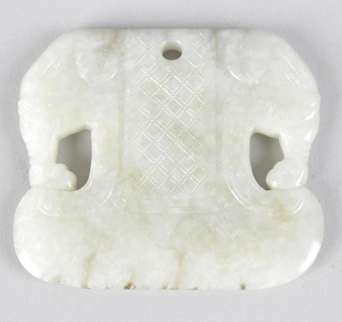 A Chinese carved celadon jade pendant. Modelled as twin
