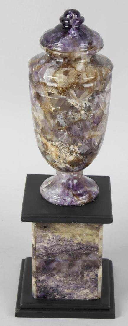 A Blue John pedestal urn. The ovoid urn with fixed