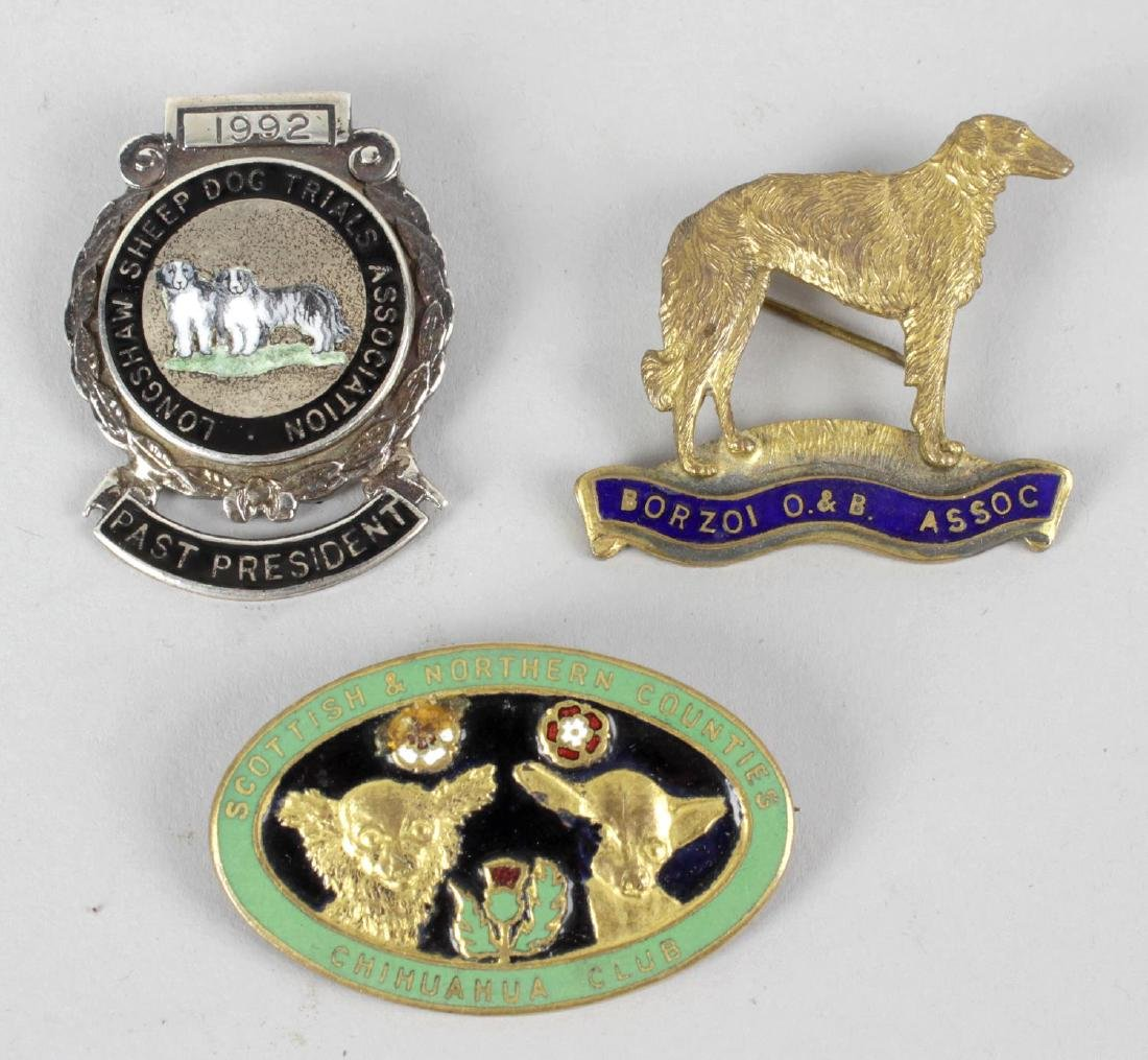 Three dog-related silver badges. The first for