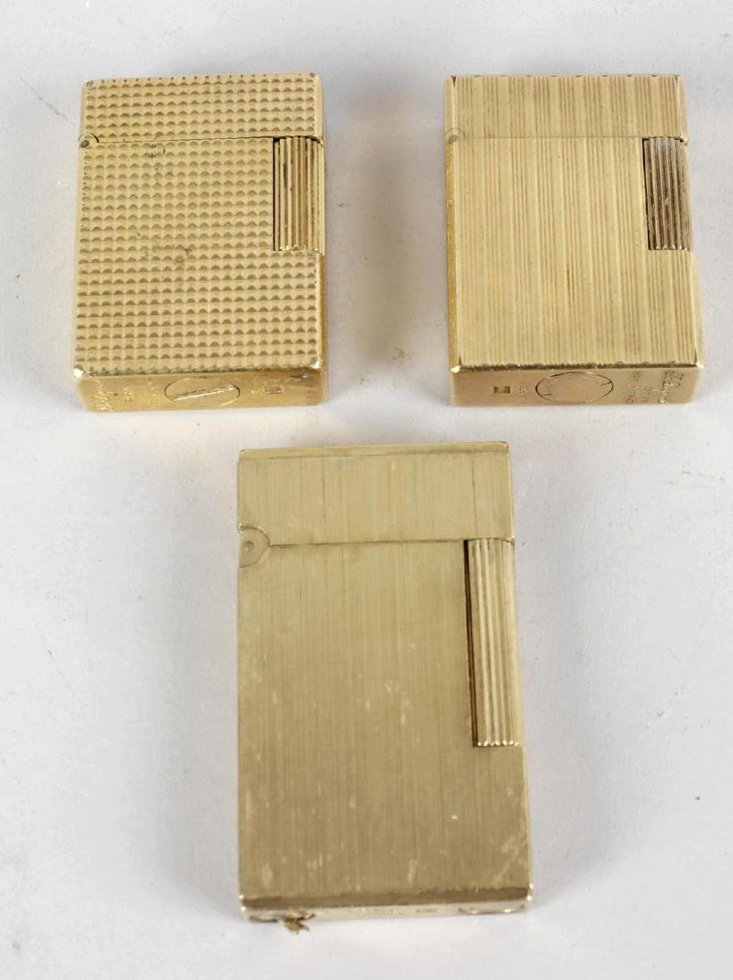 Three S. T Dupont gold-plated lighters. The first with