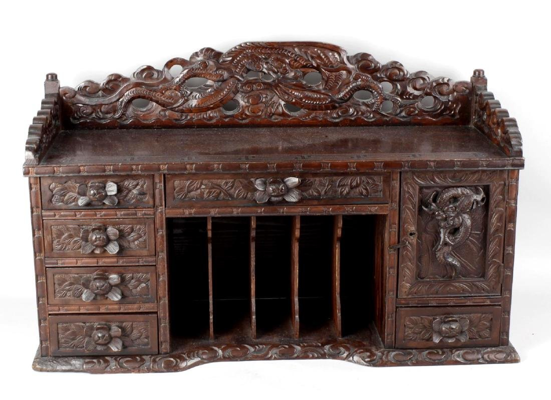 A Chinese red stained carved wooden desk top stationary